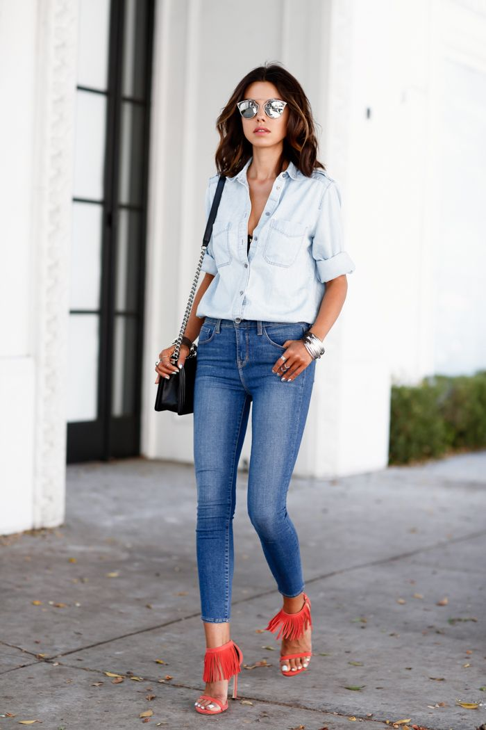 0effe3abc1248e Annabelle Fleur doubles a light denim shirt with a pair of mid-blue high  waisted denims. Her orange fringed sandals bring a modern and sexy twist to  this ...