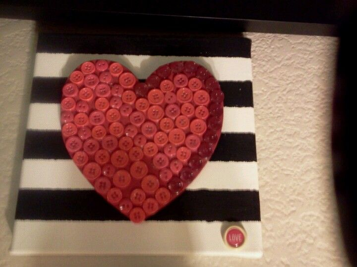 Buttons on a wooden heart in a b painted canvas
