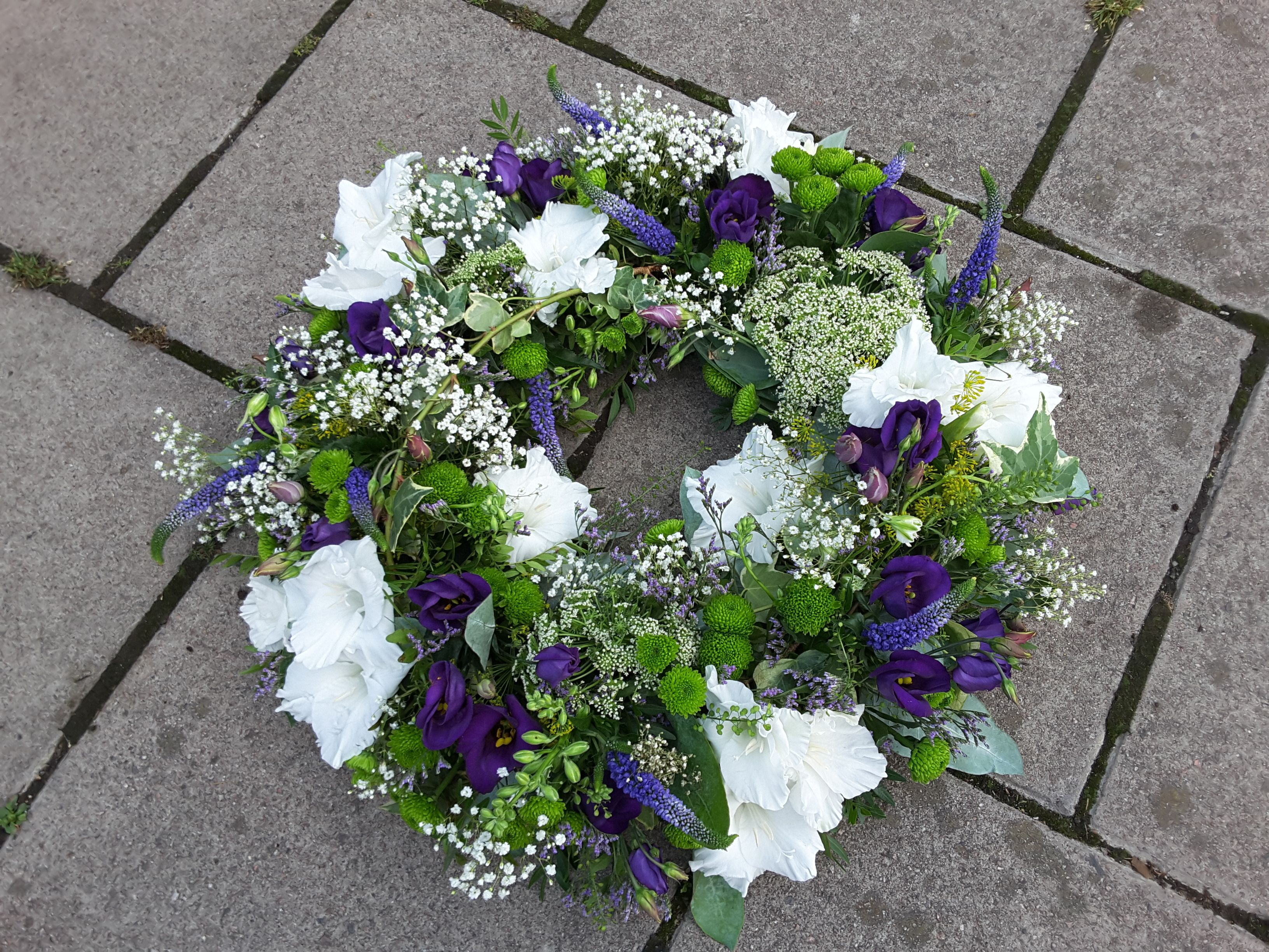Summer styled funeral wreath in whites, greens and purples