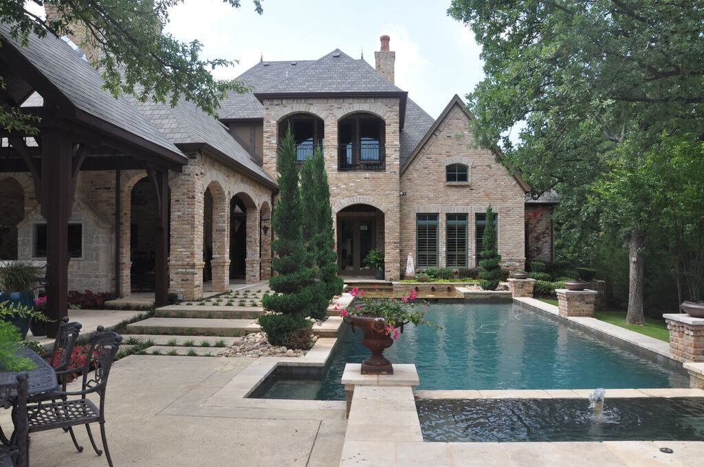 Classic pool design featuring  natural stone border, clean lines with cut outs for visual interest,  built in planters and spa.By Outdoor Signature in Argyle, TX