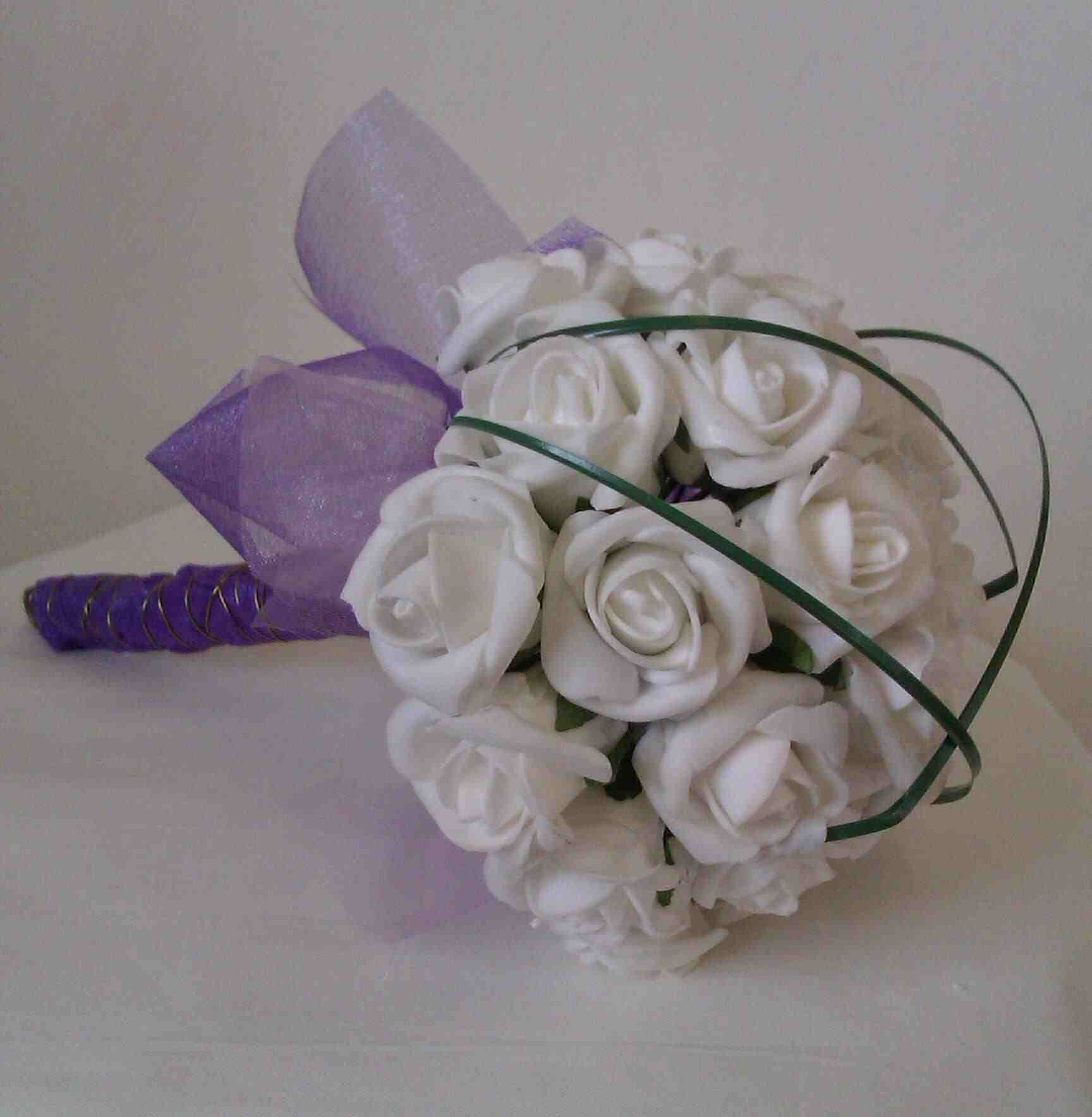 Pretty Posey Of Soft White Foam Roses With A Cage Of Bear Grass
