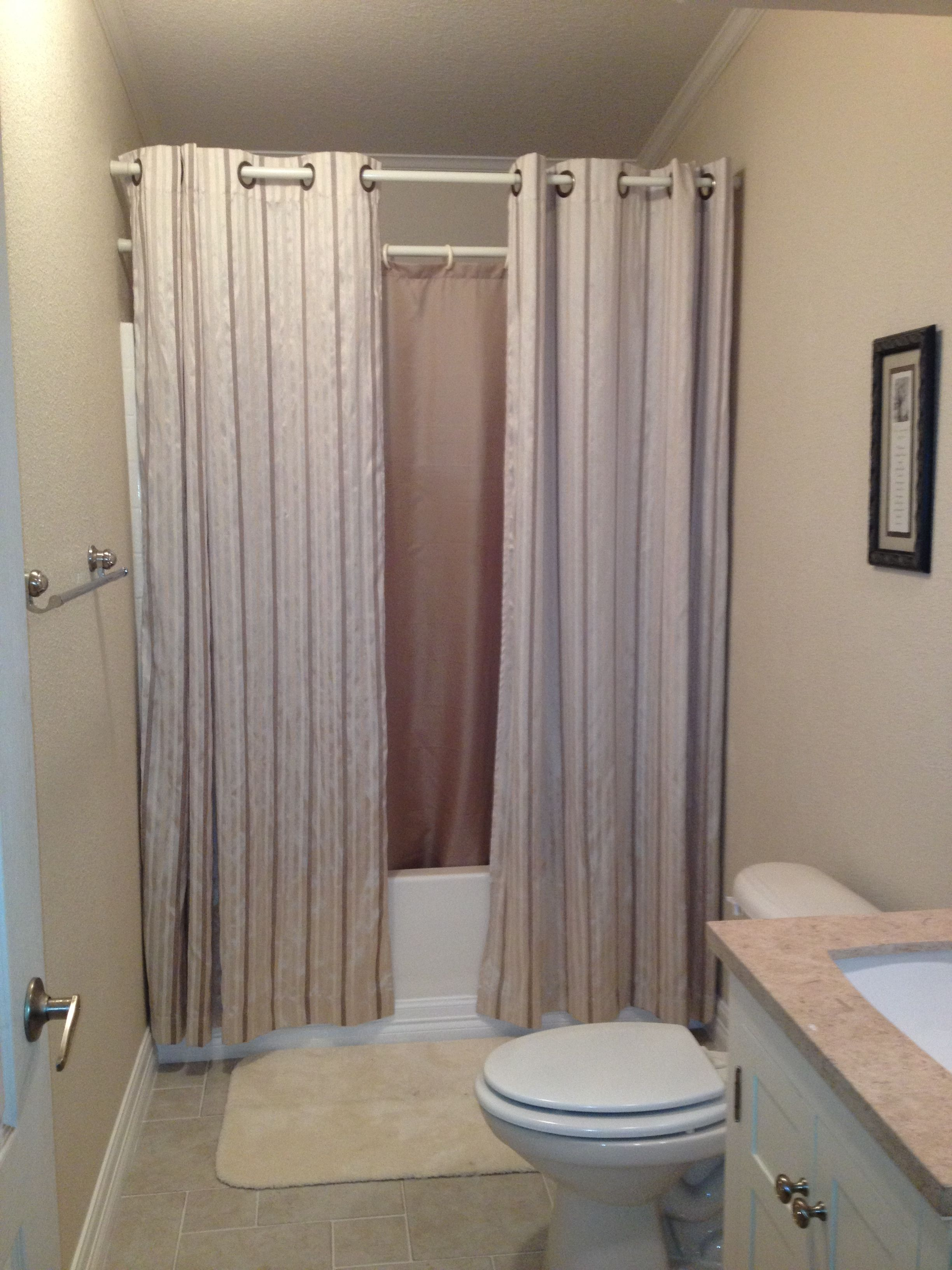 Hanging shower curtains to make small bathroom look bigger for Small bathroom high ceiling