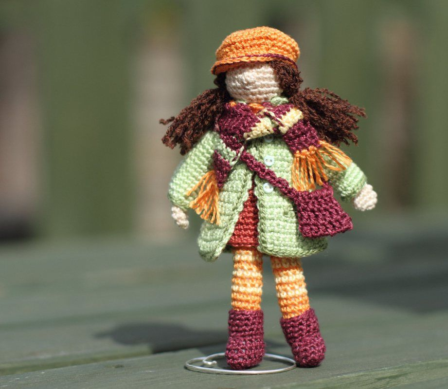 Curly doll in light green coat and orange cap