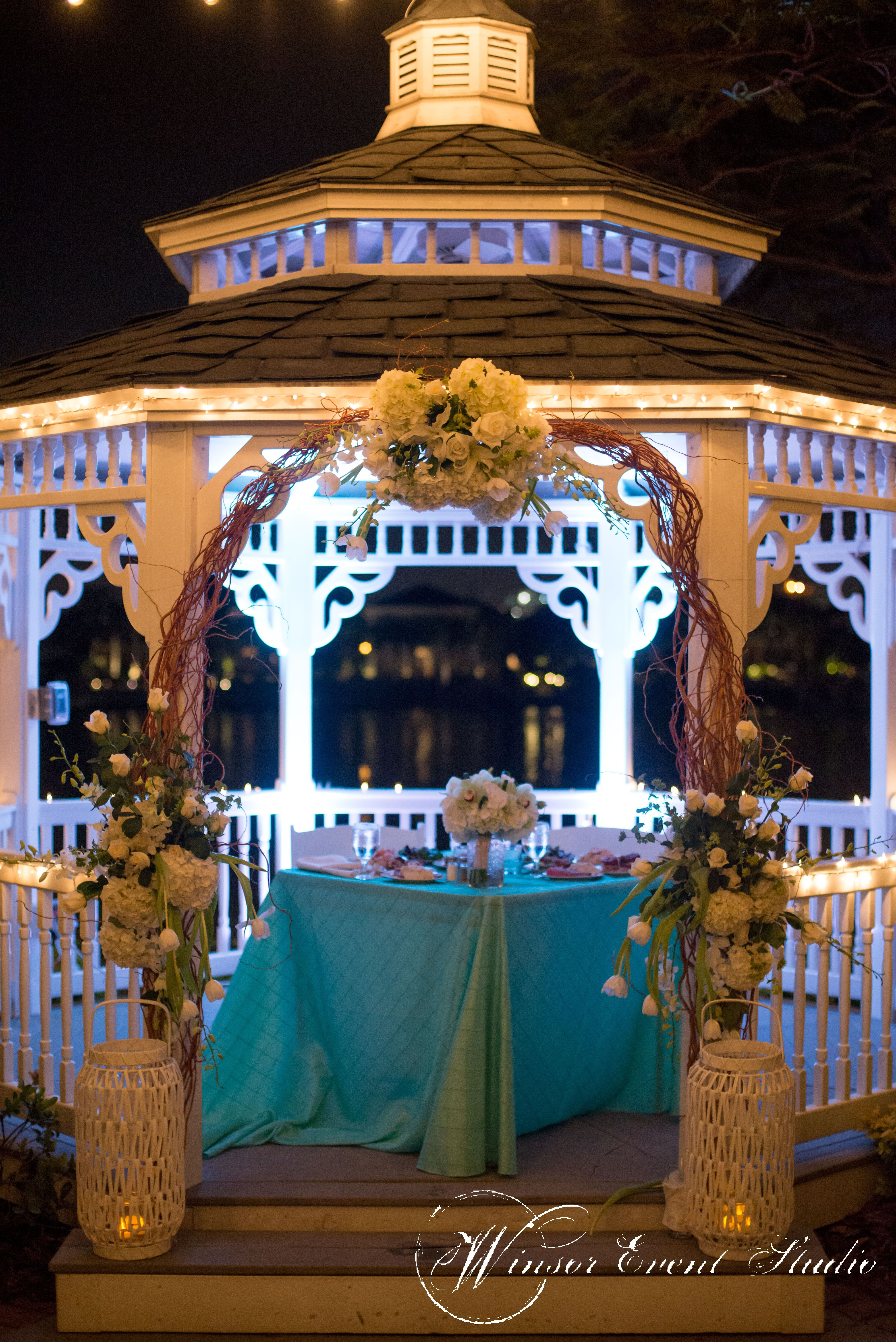 Sweetheart table placed inside the waterfront gazebo at Davis Islands Garden Club, adorned with curly willow branches and clusters of white flowers