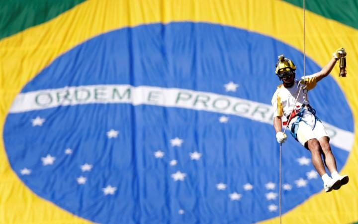 Brazilian firefighter Haudson Alves abseils with the Olympic flame as he attends the Olympic Flame torch relay at Mane Garrincha stadium in Brasilia, Brazil