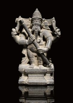 A BLACKSTONE GANESH, INDIA, PALA PERIOD, 11TH CENTURY  Carved in the round, on a rectangular plinth, wearing a tiered headdress and holding a staff - 9 1/4in (23.5cm) high