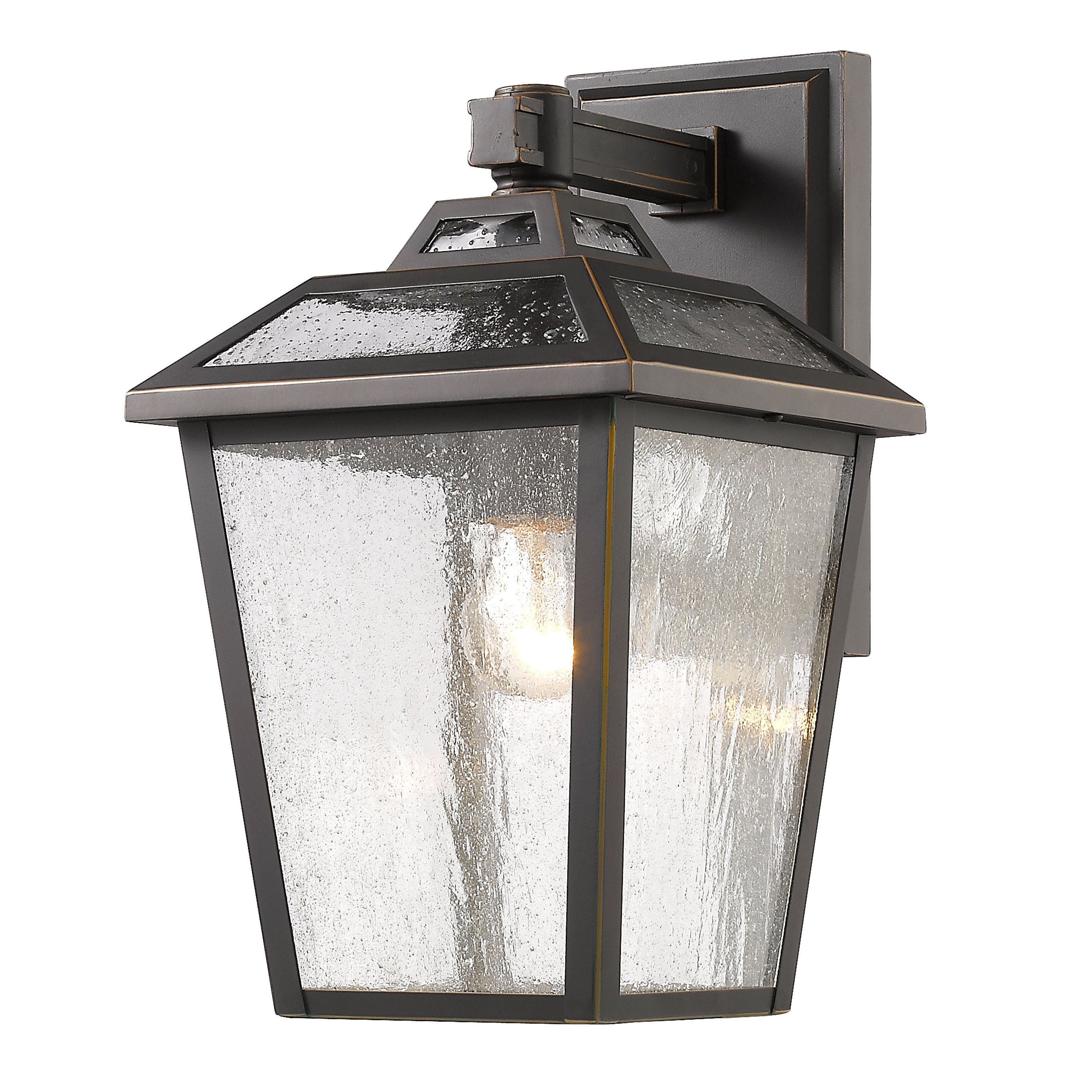 This Bayland wall light features clear seedy glass set against its oil rubbed bronze colored frame. A multi stepped top crowns this elegant fixture. This piece is constructed from high quality cast aluminum.
