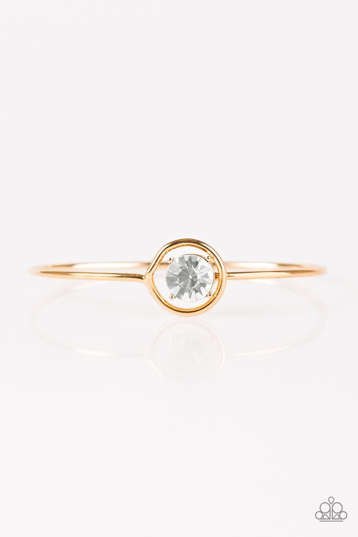 A skinny gold bar curls around the wrist, creating a dainty cuff. A ...