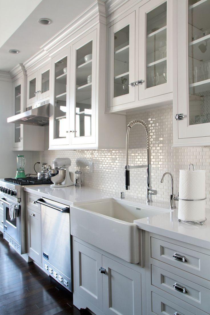 white kitchen cabinets, glass doors, dark wood floors. Backsplash ...