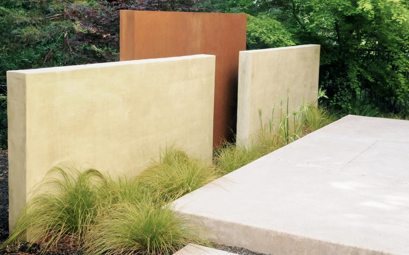 stucco or concrete walls with plants in front - maybe in front of ...