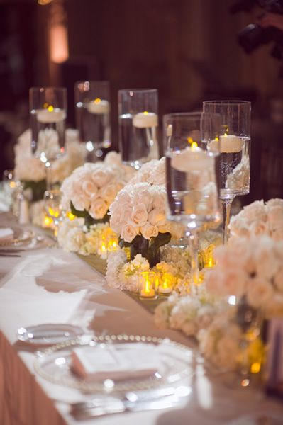 The Yellow Tea Light Give A Punch To The Traditional Table Design Of White Rose Clusters Digging The Wedding Table Decorations Wedding Table Table Decorations