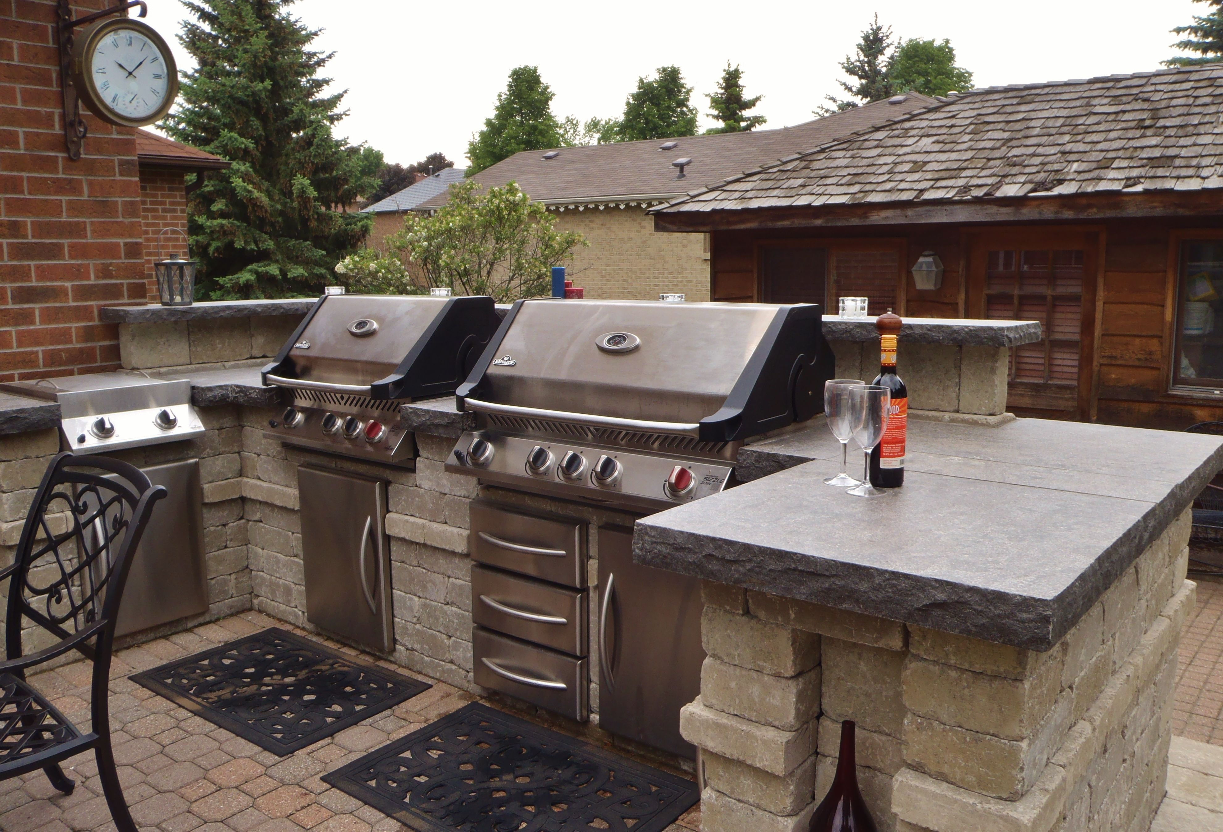 grilling station and outdoor kitchen area with backsplash and natural stone countertops on outdoor kitchen natural id=31047