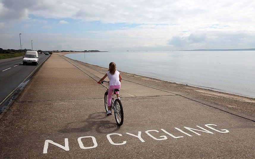 """""""A girl rides over a misspelled painted sign on a cycle path along the front of Stokes Bay, Gosport, Hampshire. Sept., 2013, caption at link"""