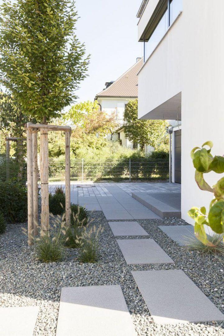 Große Platten, die am Haus entlang führen. So kommt man vom Garten zur Haustür auf ansprechendem Wege. Kies passt hier auch gut in den Vorgarten. #rinnbeton #design #gartengestaltung #modernfrontyard