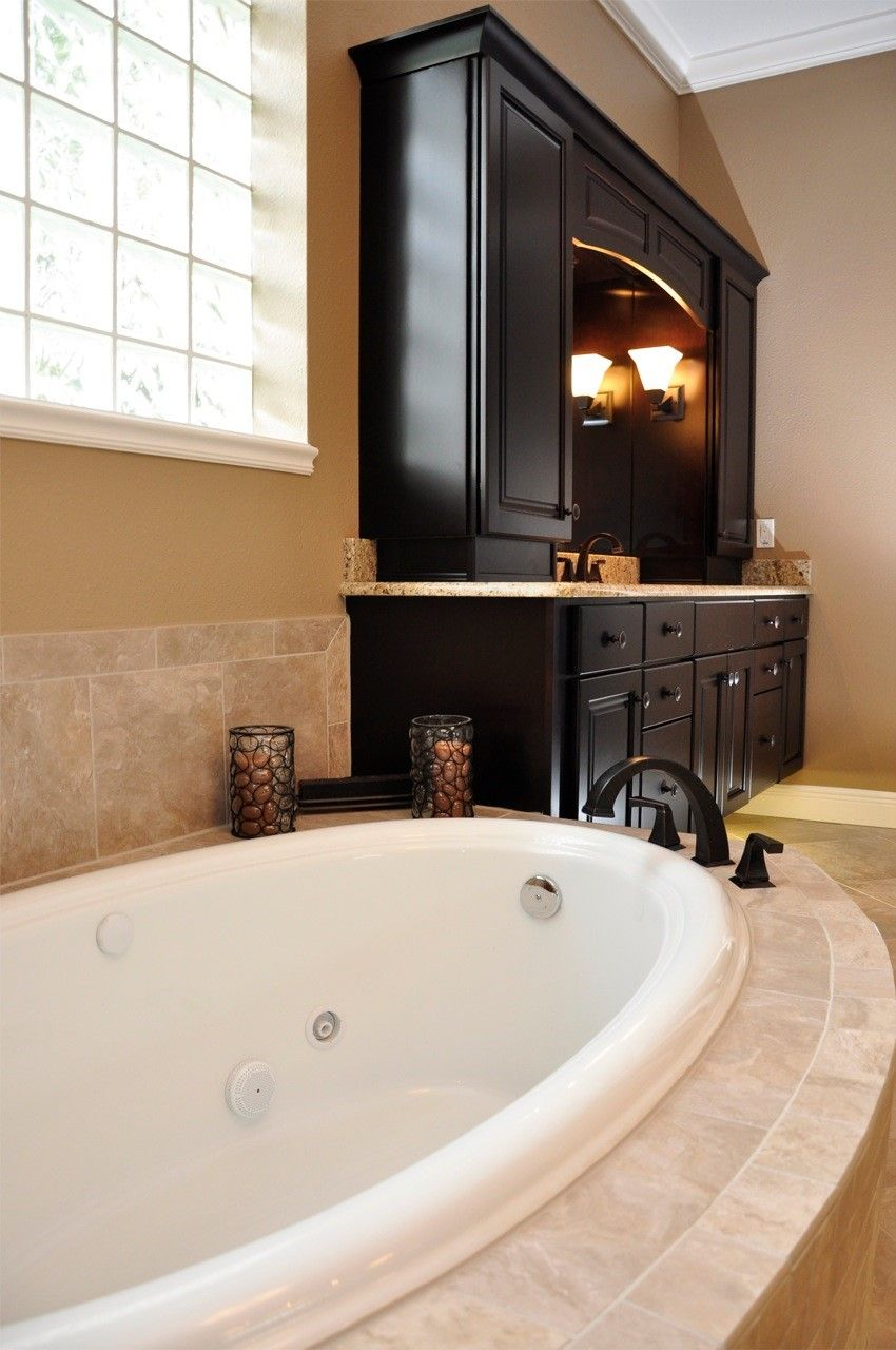 Neutral garden tub with dark cabinets and fixtures classic luxury by the best custom home for Bathroom remodeling college station tx