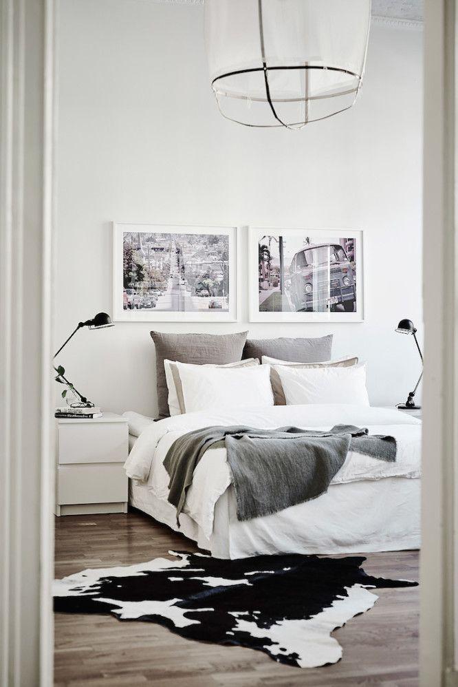 Nice Blick Ins Weiße Schlafzimmer: Großes, Gemütliches Bett Mit Schwarz Weißen  Fotos An Der Wand Und Gemustertem Kuhfell Auf Dem Boden Ideas