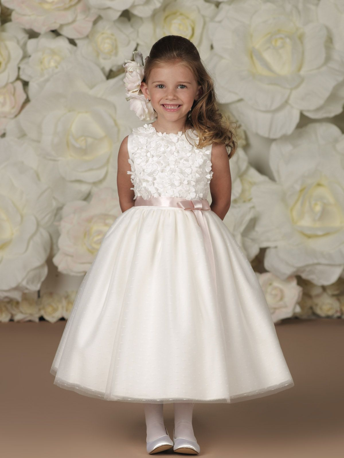Sleeveless satin, tulle, point d'esprit tea-length A-line dress with jewel neckline, tulle over satin bodice fully covered with three-dimensional taffeta flowers, double faced satin ribbon waistband, tulle and point d'esprit overlay full dirndl skirt.