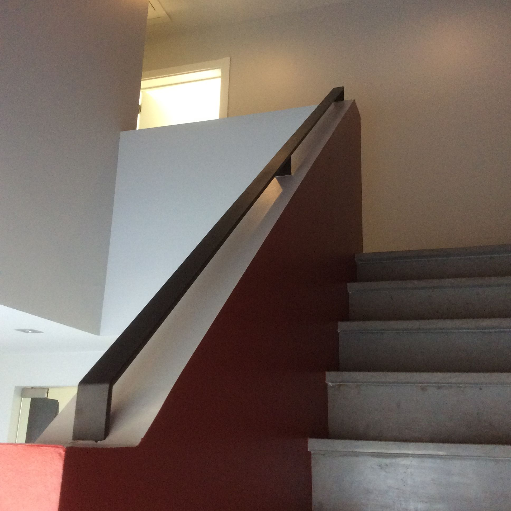 De strakke stalen trapleuning in zwarte structuurlak van buiten wordt ook binnen ge ntegreerd om - Moderne trap kwartslag ...