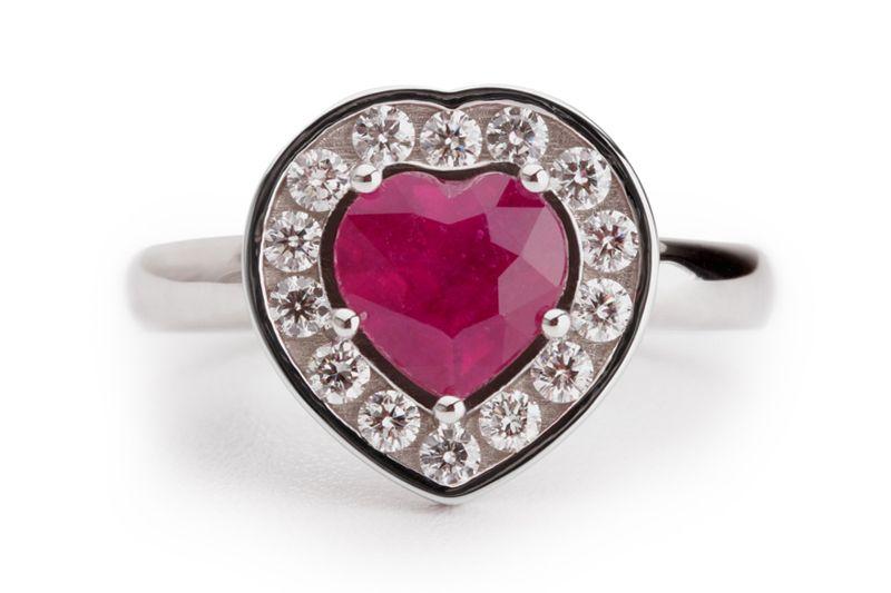 Een witgouden ring met een dieprode hartvormige robijn. De robijn is gezet tussen vijf ronde zetpootjes. Rondom de robijn zijn diamanten in een railzetting geplaatst in een witgouden hart.