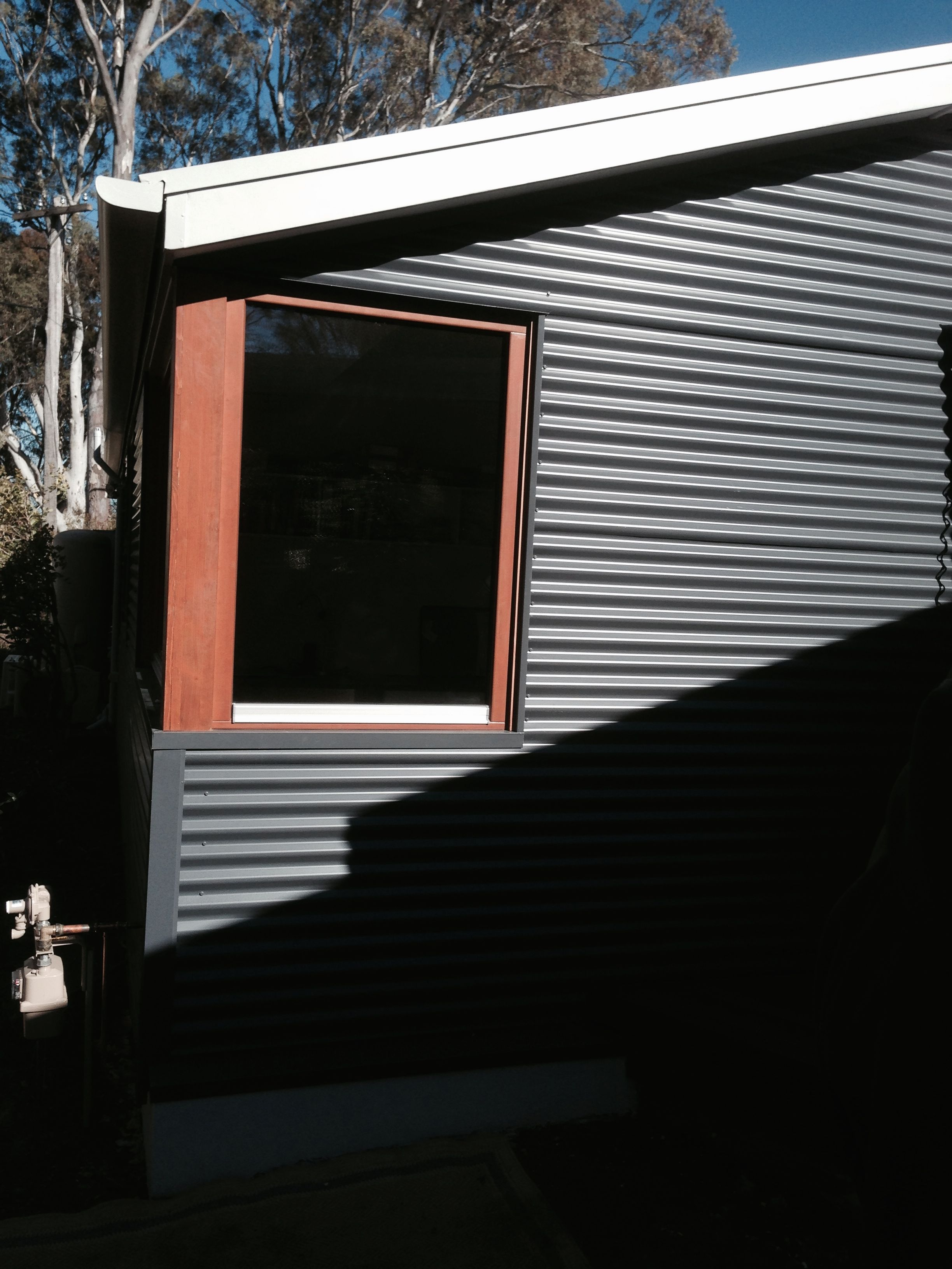 colorbond grey sheeting (wide) used with timber windows
