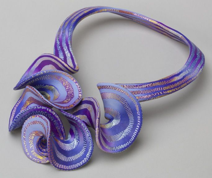 "Elise Winters created this cascade Ruffle necklace. ""My current work in polymer affords me the opportunity to merge manipulating thickness and texture, twisting, pulling and shaping clay while exploring light and color. The result is a seductive convergence of additive and subtractive color mixture allowing me to play with all the dimensions of color and light over the surface of my jewelry.""  Size: 11 x 7 1/2 x 1 inches, $2,800.00"