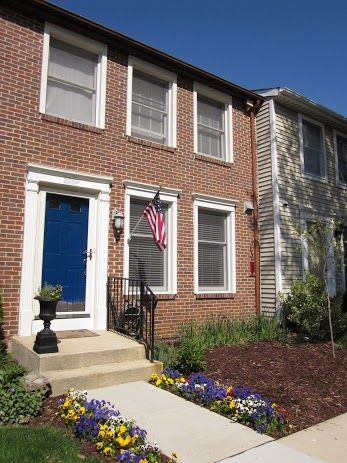 Brick Townhouse Front Yard With A Blue Door And Mulched Yard