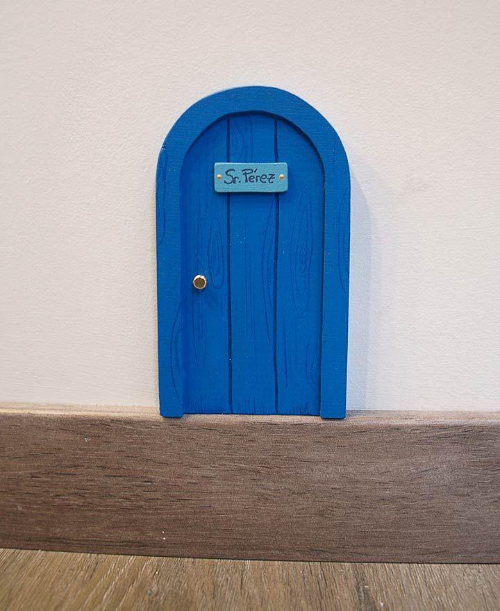 Puerta azul para el ratón Pérez. Con forma redonda, como las típicas ratoneras. Esta puerta solo puede ser abierta por la magia del Ratoncito Pérez. Ilustrada imitando la veta de la madera. Un puerta para el ratoncito Pérez con diseño original de La iluminista.