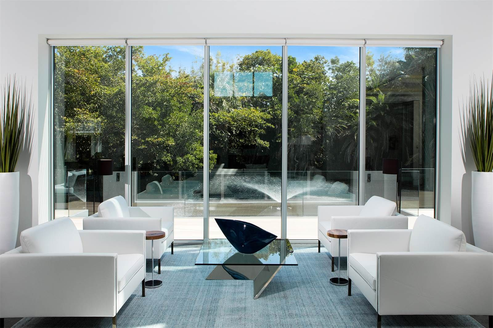 Minimalist window shades enhance the view by blending in with the homes contemporary interior