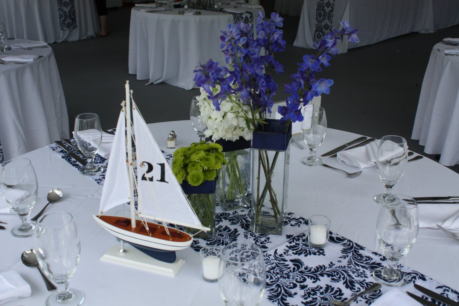 Pretty glass and flower center piece with small sailboat for table number