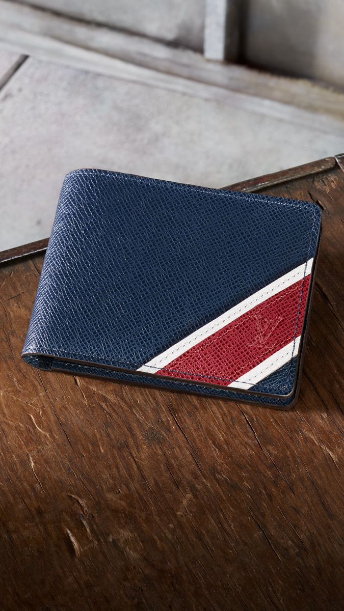 7caded9ae76 Louis Vuitton Multiple Wallet in Taiga Leather embellished by a stripe  animation inspired from the historical painting on trunks.