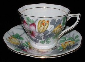 This is a Rosina, England cup and saucer with a design of hand colored on grey transfer or transferware spring flowers and shamrocks including what could be crocus but might be tulips with gold trim and hand applied enamel paint accents.