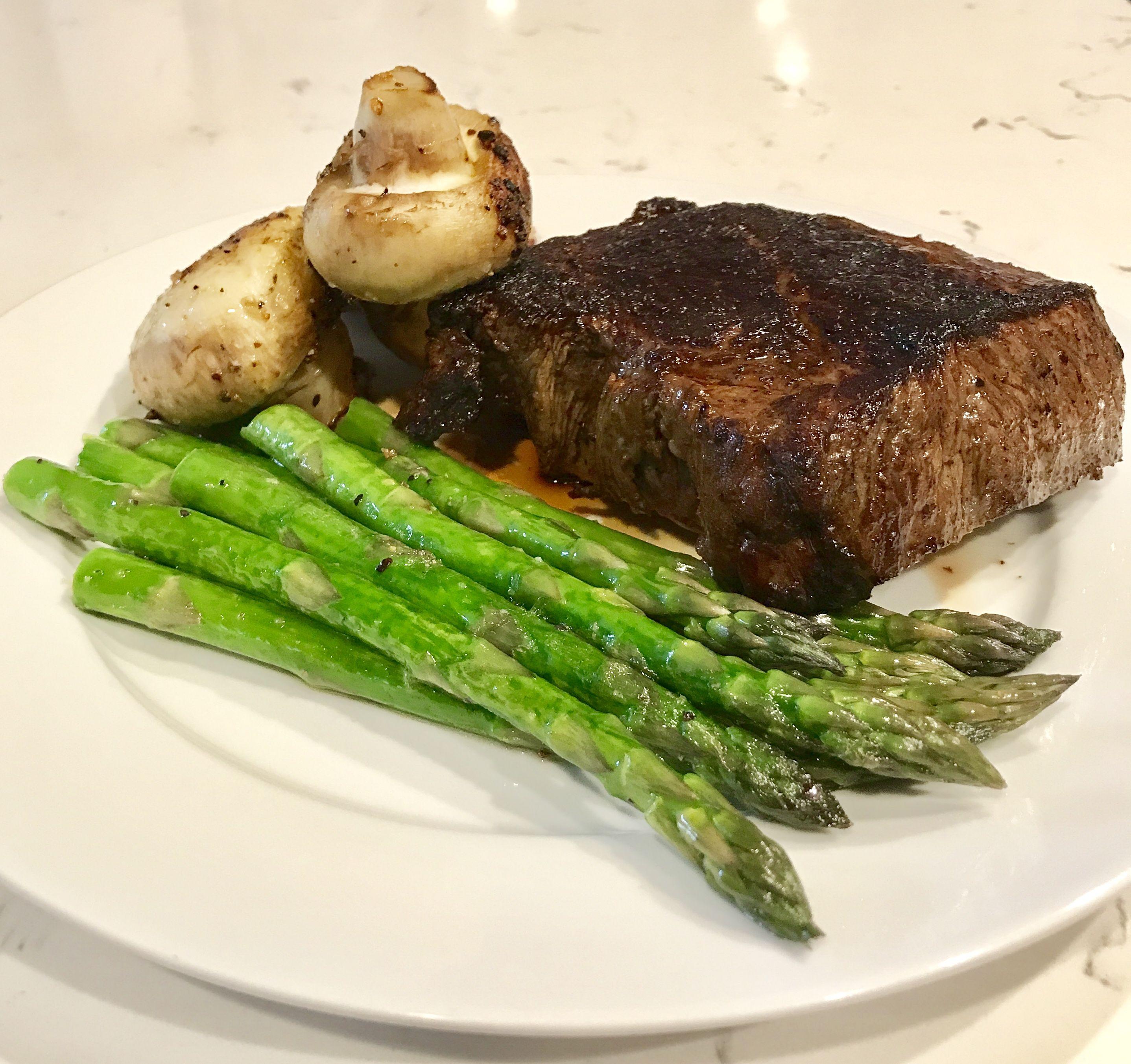 Sirloin steak dinner served with sautéed asparagus and ...