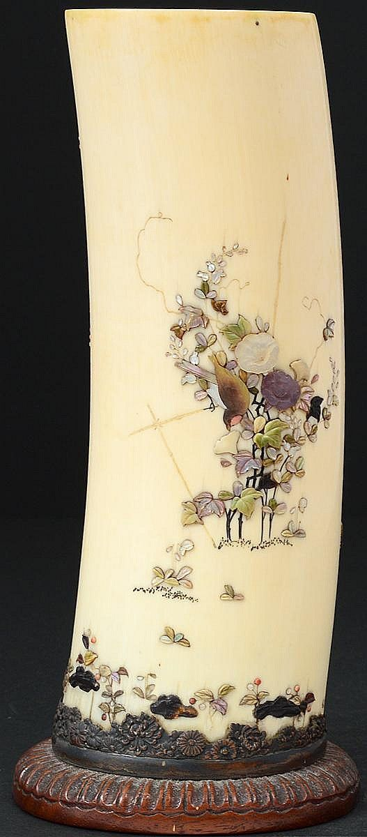 """IVORY SHIBAYAMA VASE -Japanese. Meiji-Period. 19th Century. Signed with a mother-of-pearl seal. Of tusk form, inlaid and overlaid with various stones, mounted on a wood base. Height 9 1/2""""."""