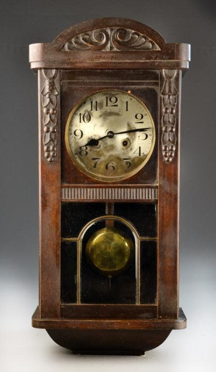 antique german pendulum wall clock carved arching conice and walnut case with beveled and leaded