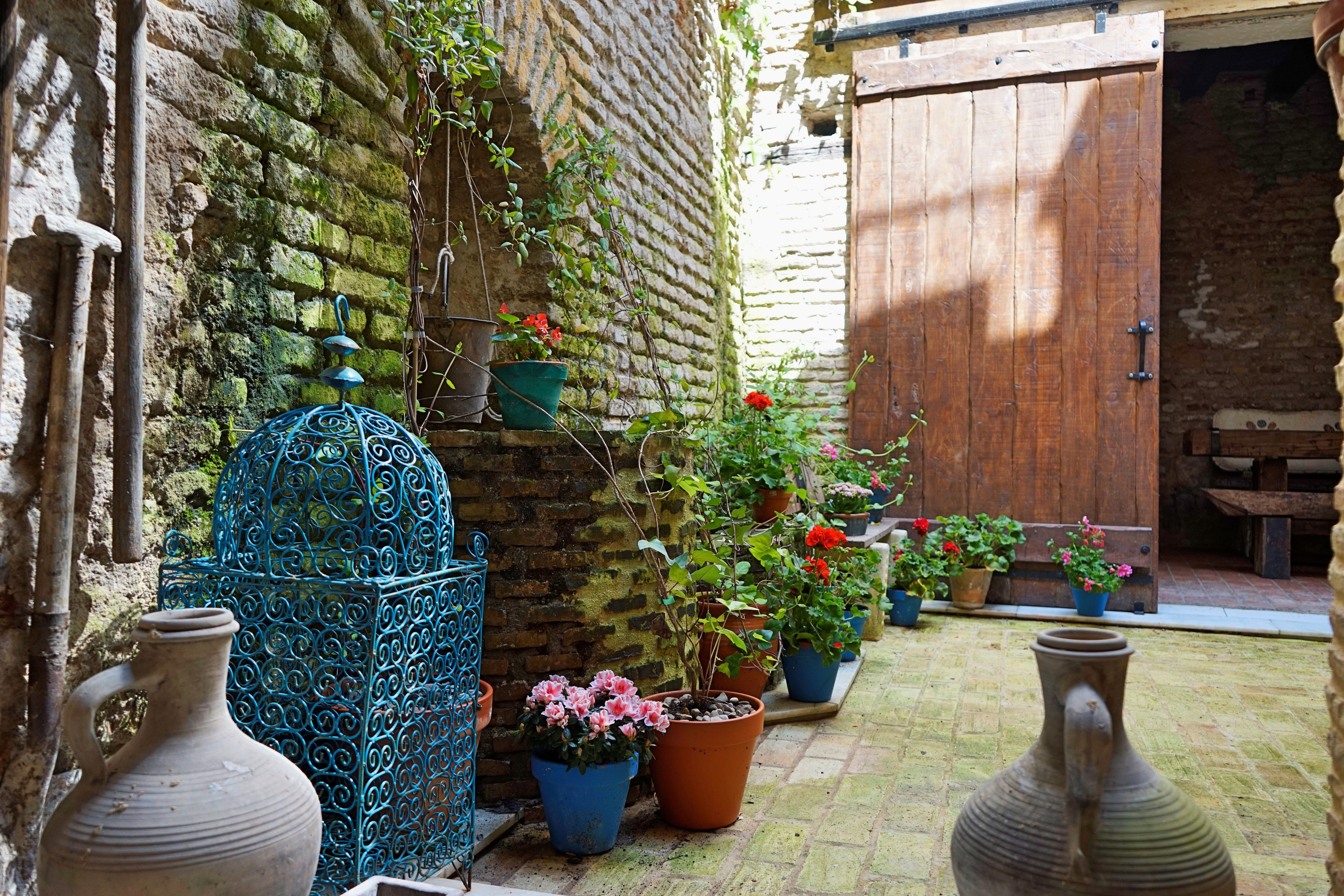 rustic spanish patio courtyard opened to the air with distressed stone brick walls diy brick water well diy brick water fountain rustic rusted bucket