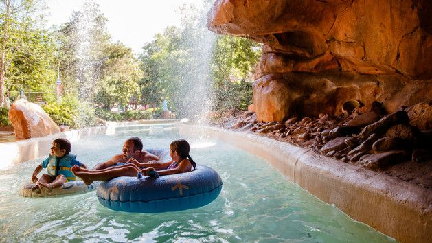 A dad and his 2 kids in a separate inner tubes chill out near a waterfall on Cross Country Creek