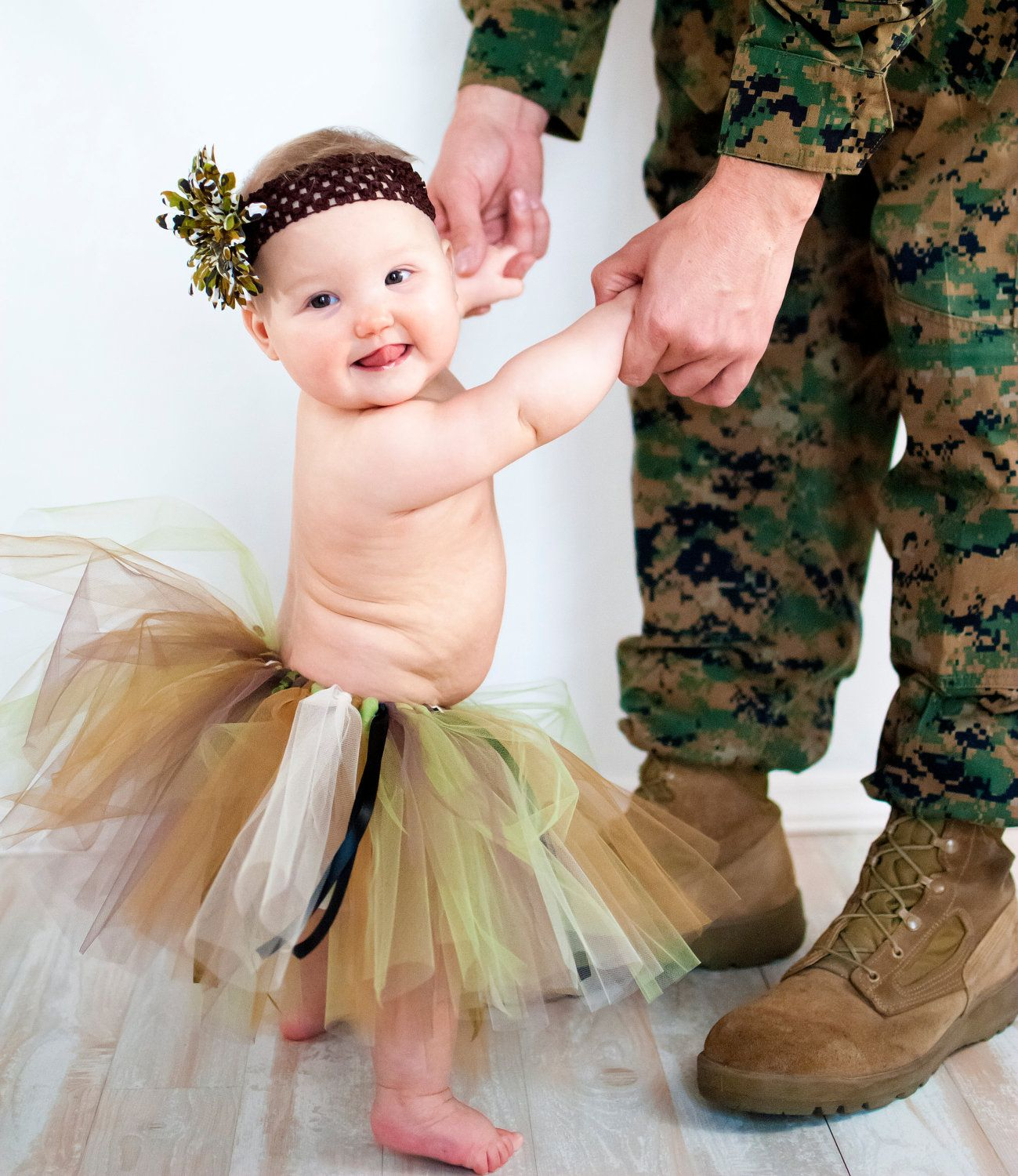 Cute baby girl in a Camo Tutu dancing with her soldier daddy