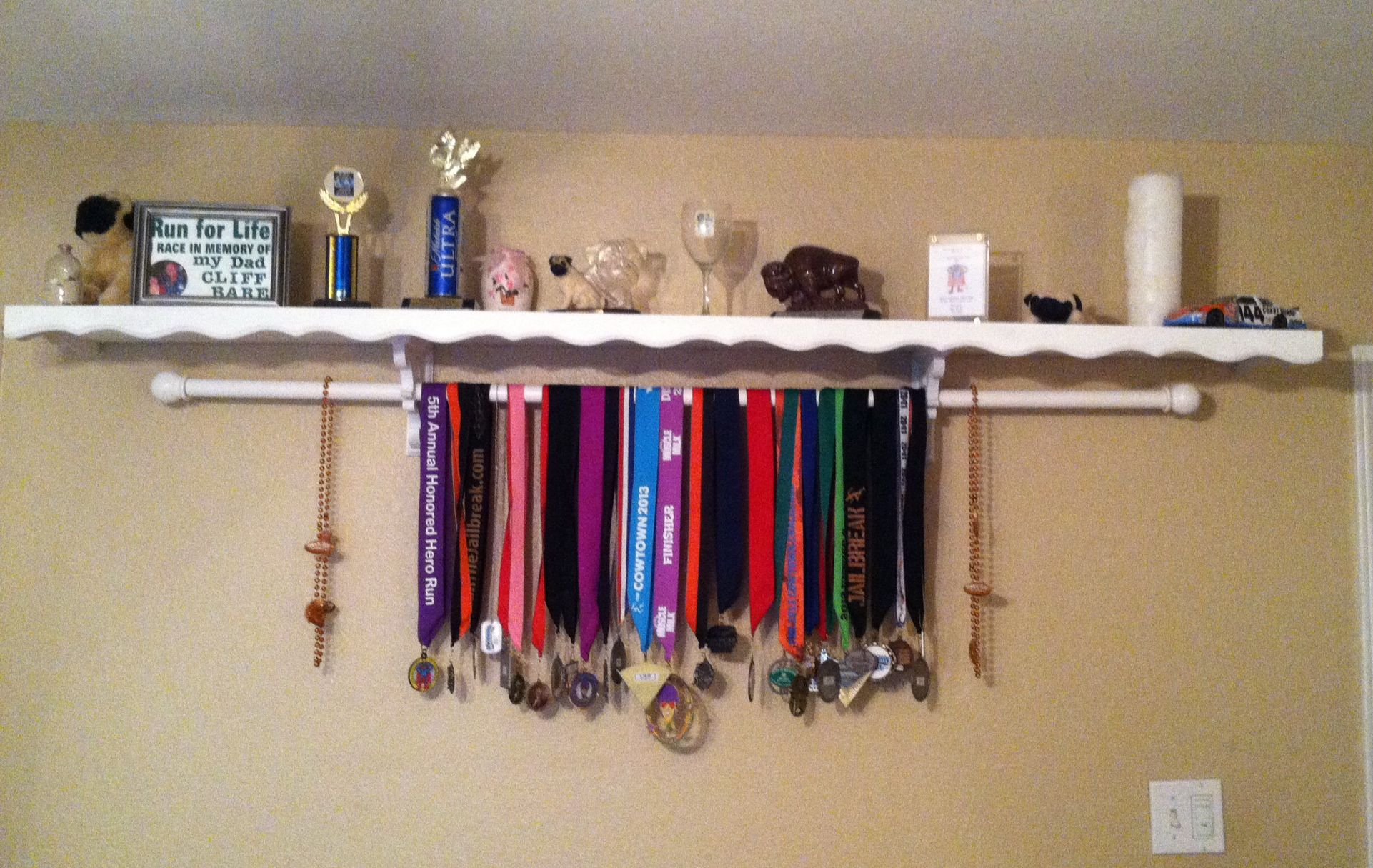 A Shelf For Trophies With A Curtain Rod Underneath To Hold