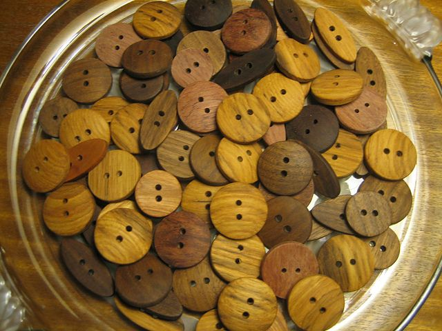 Wood Buttons. Crafted by hand into different sizes of round and oval shape, each of these buttons has been made from a variety of exotic woods including Black Walnut, Bubinga, Cherry, East Indian Rosewood, Macassar Ebony, Paduak and Teak. Hand sanded with an oil finish, some of the small details on these buttons include micro bevels on the holes to help prevent sharp edges  from cutting through delicate thread fibers over time.