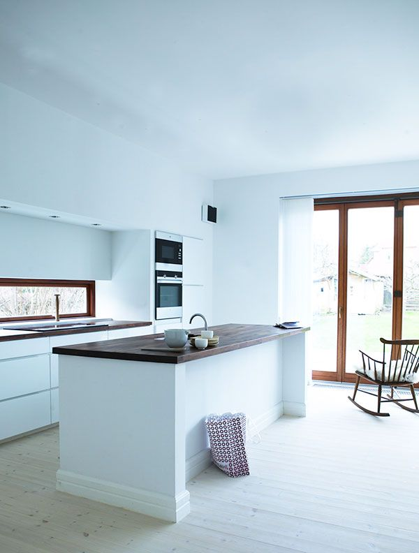 White Kitchen With Wood Counter Wall Of Windows With Wood Trim