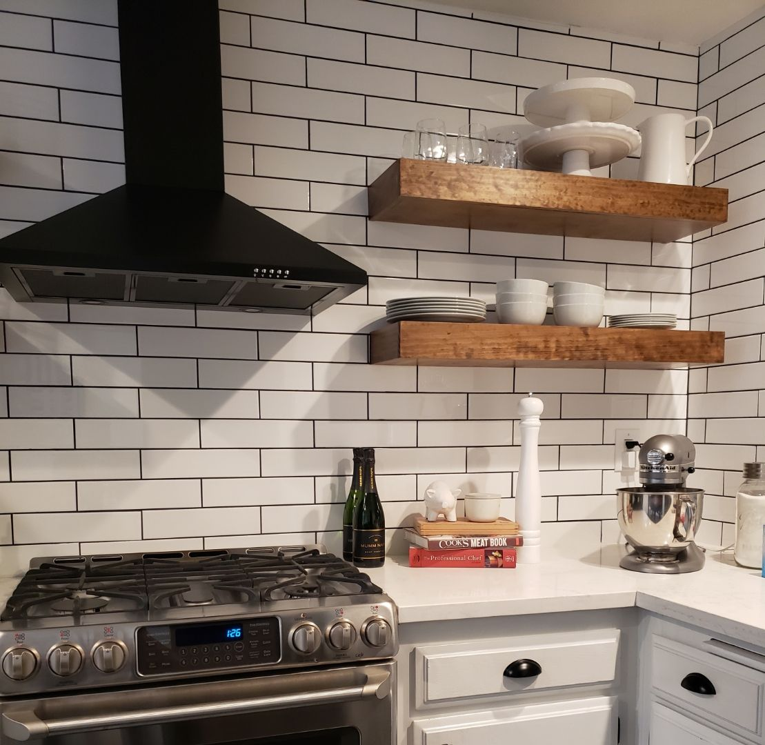 White Subway Tile With Black Grout Matte Black Oven Hood And Hand Made Floating S White Kitchen Floating Shelves White Kitchen Tiles White Subway Tile Kitchen