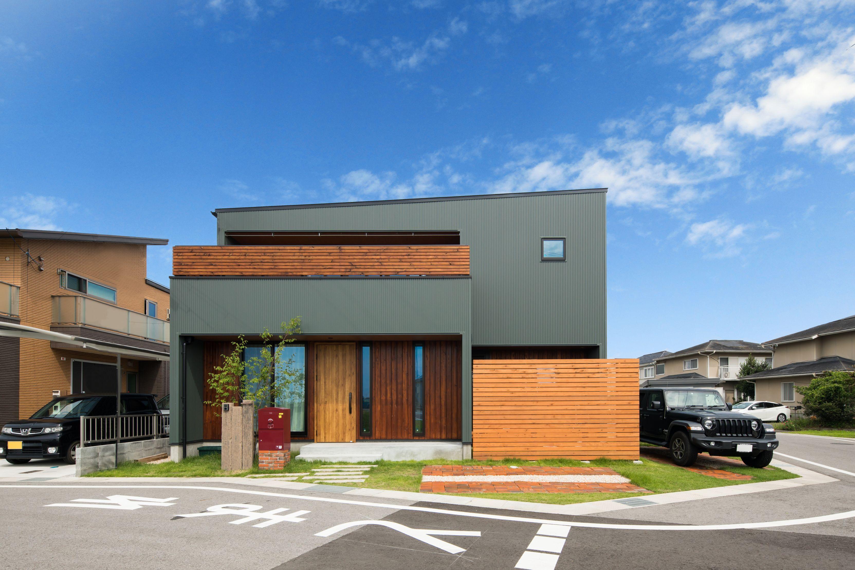 緩やかな片流れ屋根と箱型のシルエットに モスグリーンガルバと木の