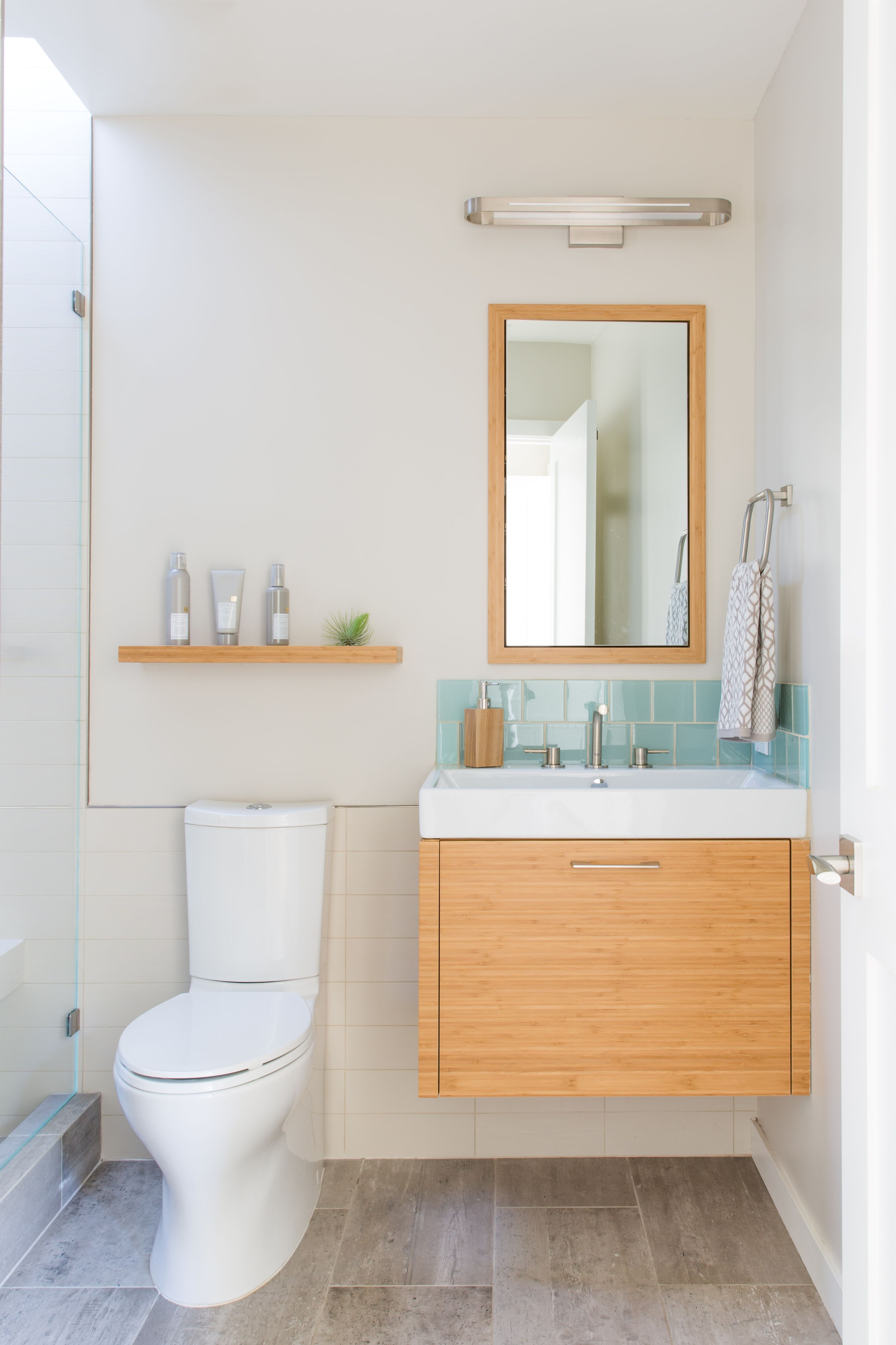 Contemporary light filled bathroom with sea green glass tile accent ...