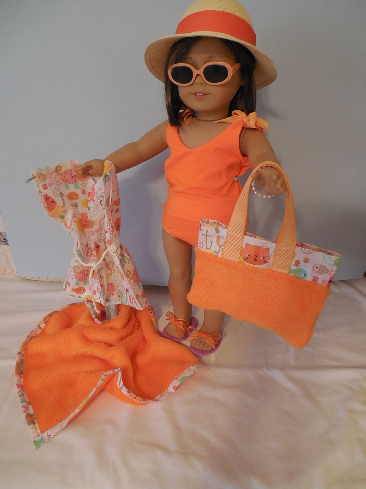 Brooke is ready to hit the beach in her orange tankini with matching beach bag, towel, and cover-uo.