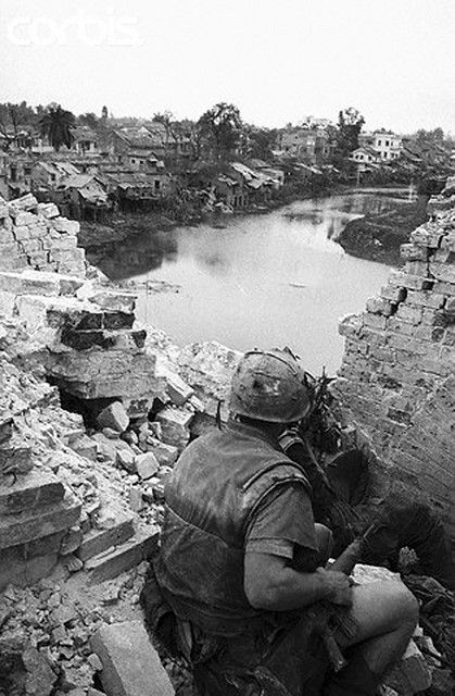 14 Feb 1968, Hue, South Vietnam --- From an elevated position behind a shattered wall, two U.S. Marines scan a string of shacks along a canal in Hue, as they look for enemy soldiers to make an appearance. Allied sources reported February 18th that it may take another week to fully crush Communist resistance in Hue. --- Image by © Bettmann/CORBIS https://flic.kr/p/6F2LKQ | U1583681 |