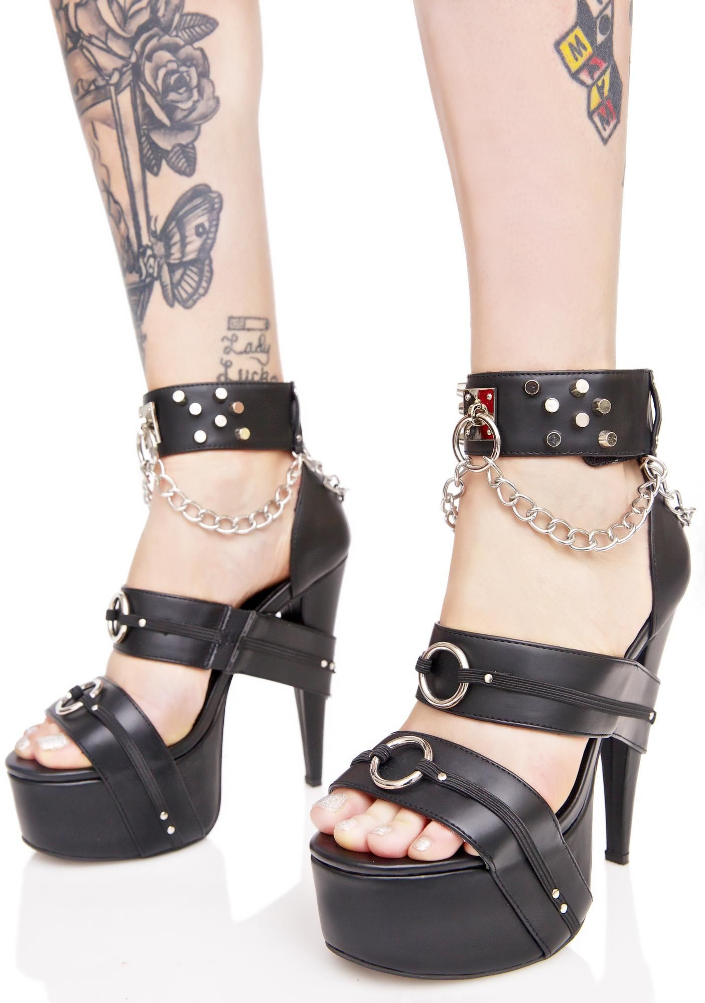 Current Mood Soma Heels cuz yer a regular at tha venue, bb~ These sikk heels feature a smooth black vegan leather construction, open toe, thick strap details with O-ring hardware that wrap around the stiletto heelz 'N platform, flat-top studs dotting the ankle strap, and drippy silver chains hanging off a centered O-ring.