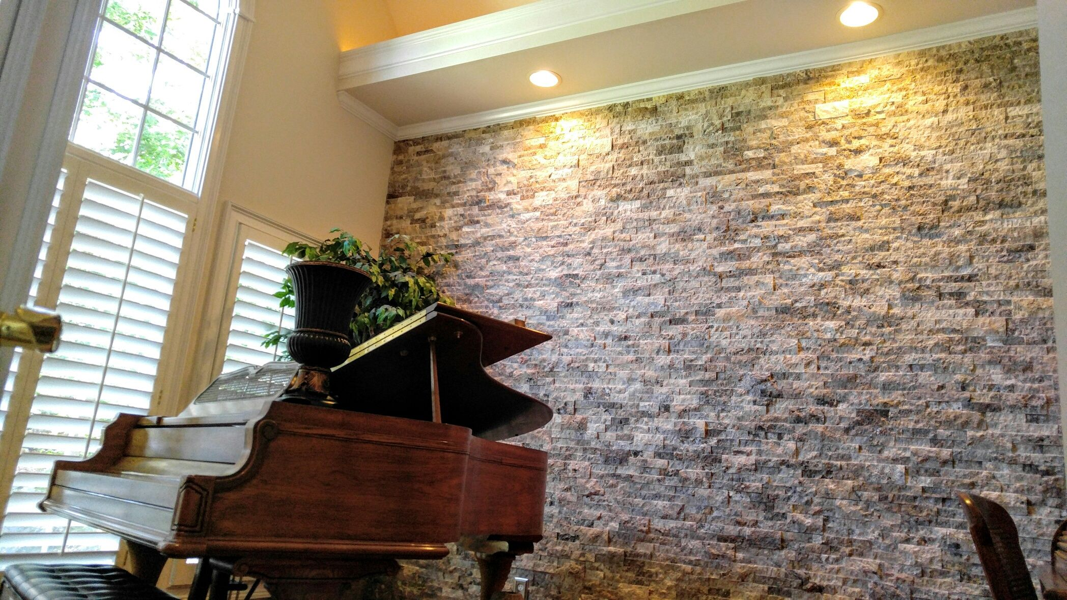 silver travertine stacked stone feature wall in a piano room