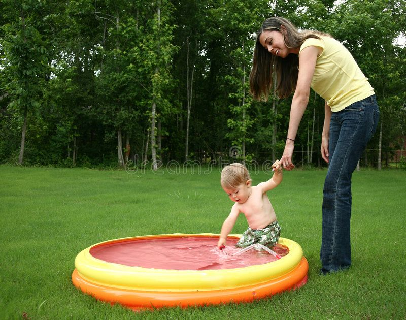 Baby In Pool. Mom and son playing outdoors in kiddie pool