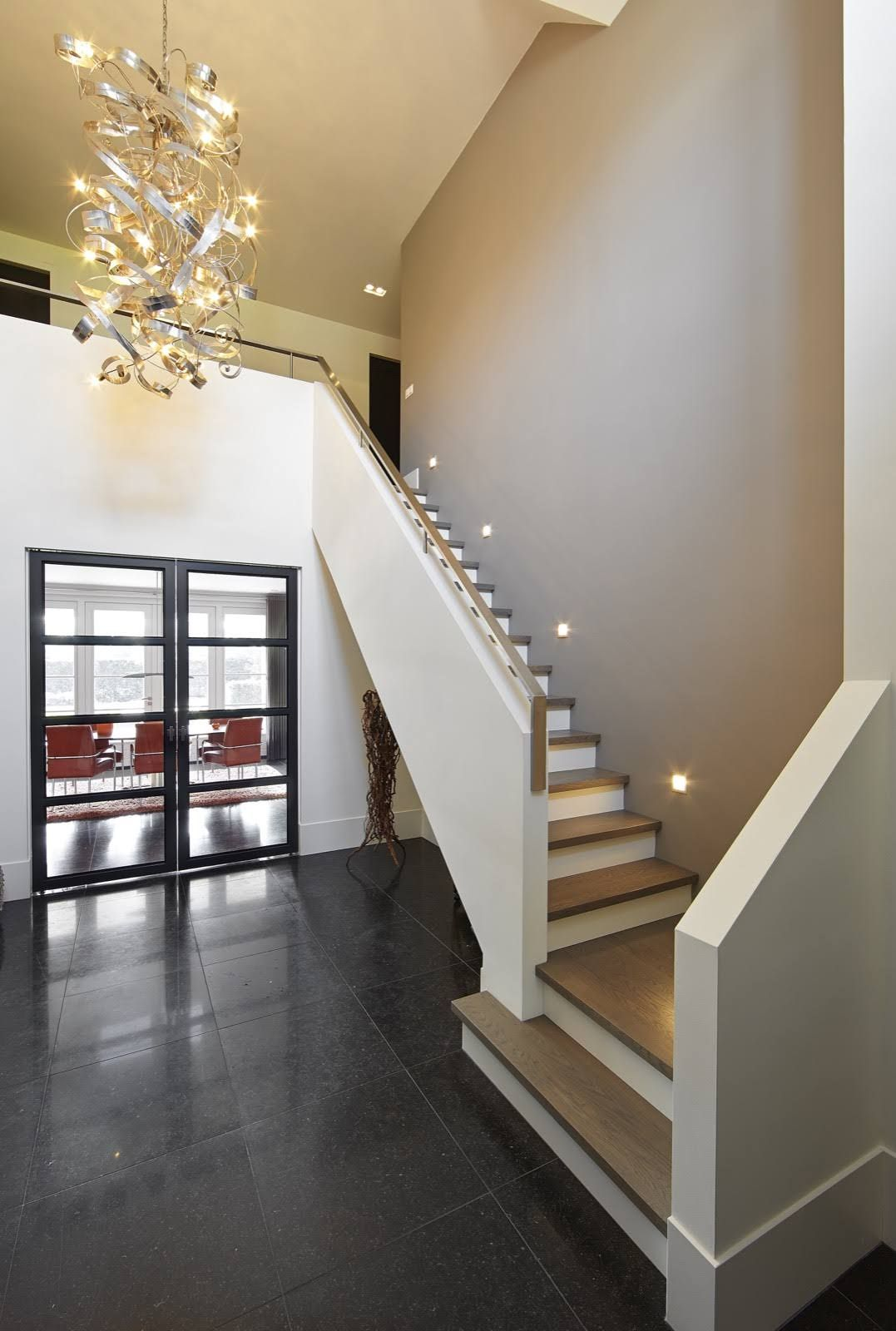 hal met houten trap met design verlichting