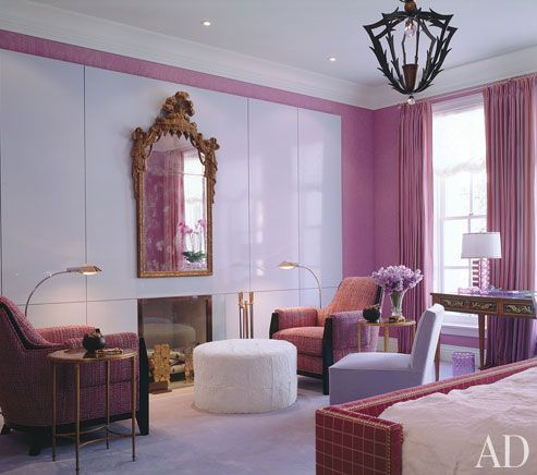 White lacquered panels are enveloped by a rosy hue in this elegant bedroom. Interior by Jamie Drake. #interiordesign #homedecor